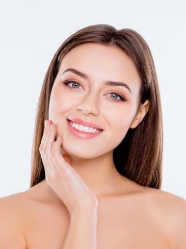 Γυναίκα χαμογελά έχοντας τελειώσει την θεραπεία απευαισθητοποίησης προσώπου στα στα Medi B in Beauty